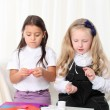 Two little girls sculpting clay on sofin room — Stock Photo #13653825