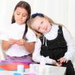 Two little girls sculpting clay on sofin room — Stock Photo #13653831