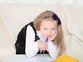 Little girl wtiting with books sitting on sofa — Stockfoto