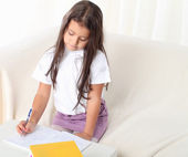Little girl wtiting with books sitting on sofa — Stock Photo