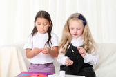 Two little girls sculpting clay on sofa in room — Stockfoto