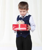 Little smart boy in suit holding redpresent box — Stockfoto