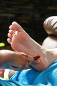 Foot massage by wood stick for urinary bladder — Foto Stock