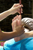 Foot massage by wood stick for frontal sinuses — Stock Photo