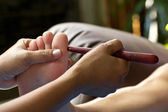 Foot massage by wood stick for nose — Stock Photo
