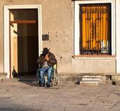 Osoba niepełnosprawna na wózku inwalidzkim zapala papierosa — Zdjęcie stockowe