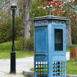 Phone booth and old lantern — Stock Photo