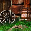 Still-life with an old wheel and barrel — Stock Photo