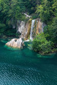 Waterfall and a large blue lake — Foto Stock