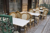 Wicker chairs and white tables — Stock Photo