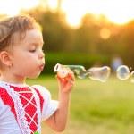 Child blowing soap bubbles. — Stock Photo