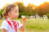 Child blowing soap bubbles. — Foto de Stock