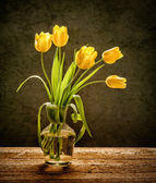 Yellow flowers on rustic background — Stock Photo