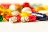 Färgade piller, tabletter och kapslar på en vit bakgrund — Stockfoto