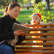 Happy mother and her child looking at tablet PC in park — Stock Photo #34726923