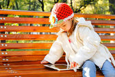 Happy child with tablet PC on a bench park — Stock Photo