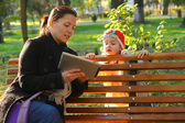 Happy mother and her child looking at tablet PC in park — Stock Photo