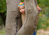 Sweet toddler girl looking behind the stone tree — Stock Photo