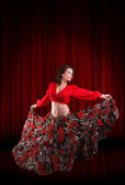 Woman traditional dancer wearing red dress on the dark red stage — Stock Photo