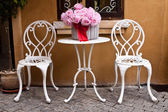 Vintage chair and table with flower in front yard — Stockfoto