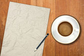 Paper and a white coffee cup on a wooden desk — Stock Photo