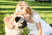 Cute girl hugging with lovely dog at the park on summer day — Stock Photo