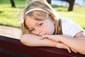 Child problem. sad little girl sitting alone at the park — Stock Photo