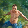 Young attractive man staying in the sea - Stock Photo