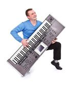 Happy man playing on synthesizer — Stock Photo