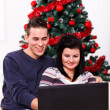 Christmas couple with laptop — Stok fotoğraf