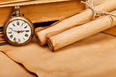 Antique pocket watch and paper rolls — Stock fotografie