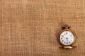 Classic pocket watch on burlap — Stockfoto
