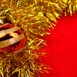 Christmas globe on golden  tinsel — Stock Photo