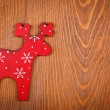Stock Photo: Red raindeer on wooden background