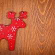 Red raindeer on wooden background — Stock Photo