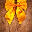 Yellow ribbon on wooden background — Stock Photo