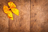 Yellow ribbon on rustic wooden background — Stock Photo