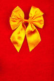 Yellow ribbon on velvet background — Stock Photo