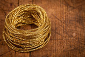 Golden rope on wooden table — Stock Photo