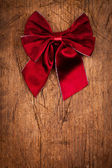 Claret bow on wooden table, Christmas decoration — Stock Photo