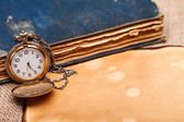 Pocket watch with antiquities — Stock Photo