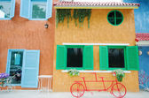Red bicycle infront of colorful building background — Stock Photo