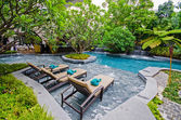 Poolside relax chairs in garden style swimming pool — Stock Photo