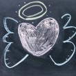 Heart angel sign drawn with chalk on blackboard — Stock Photo