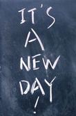 It is a new day title written with chalk on blackboard — Stock Photo