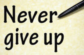 Never give up title written with pen on paper — Stock Photo