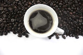 A cup of coffee and coffee beans background — Stock Photo
