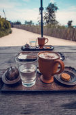 Xícara de café, um copo de água e biscoitos em cima da mesa de madeira. — Foto Stock