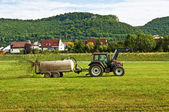 Tractor throwing dung — Stock Photo