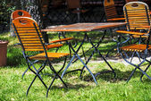 German beer garden with wooden furniture — Stock Photo